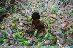 BANGLADESH, Dhaka: A Bangladeshi youth sorts through polyethylene terephthalate (PET) bottles for recycling in poor working conditions in Dhaka on August 21, 3013. PET bottle flakes are an exportable raw material from Bangladesh. The recycled material is used toproduce PSF (Polyester staple fiber) which are then made into PSY (polyester spun yarn) or used as stuffing materials. AFP PHOTO / Munir uz ZAMAN