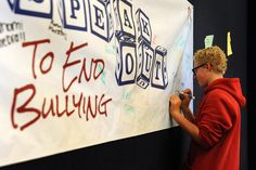 Ninth grader Matthew Hanning, 14, signs a banner petitioning against bullying Oct. 2 at Sand Creek High School in Falcon School District 49. Student council freshmen representatives were handing out markers to sign the banner, along with anti-bullying bracelets and ribbons. The two-color ribbons symbolized that one out of four students are eventually confronted by aggression or harassment in school, based on nationwide statistics.