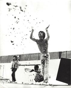 UNKNOWN - MICK JAGGER 1973 tour, in jumpsuit designed by OSSIE CLARKE. Ossie had to make several jumpsuits for each tour because they didn't last long. Each one had hundreds of sparkly silver-toned circles or squares so they would glitter on stage. – Courtesy Calderwood Gallery