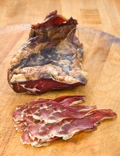 "Lamb ""Prosciutto"" (Sliced)(Salumi Artisan Cured Meats - Seattle, WA) - Boneless lamb leg, cured and aged to intensify the lamb flavor. Delicious and a beautiful shade of red. Wonderful with deep red wines."