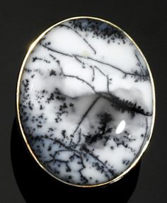 """Dendritic Opal Ring  India   The seepage of iron oxides and other impurities into the silica which comprises common opal can produce some surprisingly beautiful branching """"fernlike"""" or dendritic patterns as seen in the present ring. The oval cabochon of white opal with black dendrites, measuring 33.0 x 27.0mm, is bezel-set in silver"""