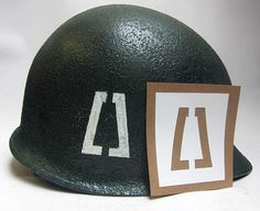 Soldiers from the 77th have served in most every major conflict and contingency operation from WWI, to World War II, and several gave their lives on 11 September 2001. During WW2 they fought in the Western Pacific, Southern Philippines and Ryukyus campaigns.   This is a variation stencil for the 77th Infantry Division during WW2. The original had yellow paint and the two 'tabs' were paint in, to make a cut off pyramid shape.   www.warhats.com