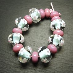 'Candy' Ditsybeads Effetre opaque Light Turquoise 232 encased with Effetre Super (Crystal) Clear 006, decorated with flowers in Effetre White 204. Spacers are Reichenbach 104 Opal Raspberry.