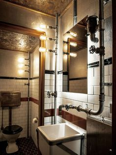Baño decorado e instalado con tuberías a la vista.