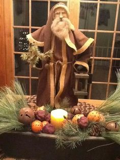 Arnett santa with greens and oranges and candlelight