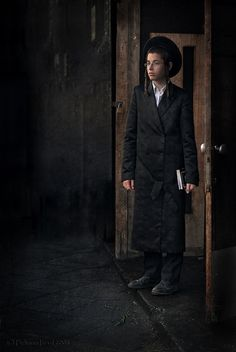 A young teen Jewish ultra-orthodox waiting quietly in the entrance of the synagogue