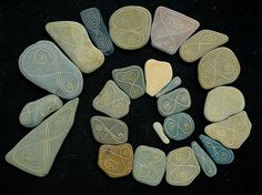 24 flat stones (except the second one) painted with 'infinity'-symbol (lemniscaat). Beach Surtainville, Cotentin Normandy.