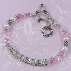 Child Name Bracelet - C04  Birthstone crystal bracelet featuring Swarovski crystals and pearls and ornate Bali sterling silver beads. This shows the C04 design with the Bali round toggle clasp and dotted heart outline charm – small letter blocks. Crystal colours – light rose and clear. Pearl colour – white.   Either a lobster clasp or toggle clasp may be chosen for this bracelet.