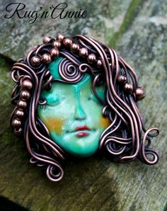 Polymer clay face with copper wire wrapping