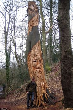 Tree treat: Artist Andy O'Neill with one of his completed tree carvings in Bedgebury Forest, Kent