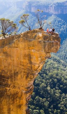 Three brave souls perched precariously on the Hanging Rock in the Hanging Rock in Victoria, Australia.