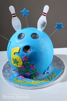 Bowling Pins & Ball #165Hobbies by Michael Angelo's Bakery | This fondant cake is covered in blue fondant and shaped like a bowling ball. It is decorated with star cut-outs and the number 5. The bowling pins are also made by hand.