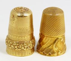 PAIR OF ANTIQUE 22KT YELLOW GOLD THIMBLES  One has a swirled diagonal border, no monogram. The other has baroque floral raised band.