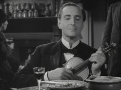 Basil Rathbone as Sherlock Holmes plucking at violin strings to annoy the flies.