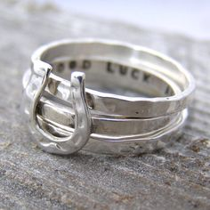 A gorgeous sterling silver personalised horseshoe stacking ring made by Ghazal for Soremi.Choose to have silver rings or go for a mixture of silver and 18ct gold plated. Please note that the horse shoe ring is £50, additional plain bands are £24 each. The combination shown in the image would total £98 The number of characters is dependent upon the size, if you are unsure if your required text will fit just send the text and ring size to me via the ' ask seller a question ' b...