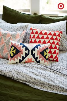 Throw pillows are a way to start experimenting with color and pattern in your bedroom. Keep things grounded with a neutral hue like olive, and a gray and white chevron print sheet set.