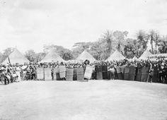 OKONDO'S VILLAGE. THE ASSEMBLED WARRIORS; OKONDO AT THE CENTRE, WITH THE LIGHT SHIELD. Locale: OKONDO'S VILLAGE, CONGO BELGE