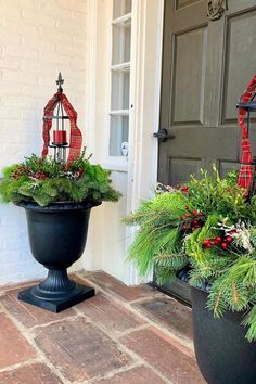 """Build your greenery tight to the bowl of the 23"""" Crescendo to emphasize height with special features such as the custom lantern candle holders, shown here. Embellish with ribbon, winter berries, boxwood, and pine boughs! Design and photo credit: Gretchen Hubbe of THRiVE Planters, Illinois. #holidayurns #holidayplanters #christmasplanter #christmasurn #winterplanter #planterdesign Lantern Candle Holders, Candle Lanterns, Candles, Christmas Urns, Christmas Planters, Winter Planter, Winter Berries, Recycled Rubber, Timeless Design"""