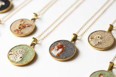 Embroidered creature pendants