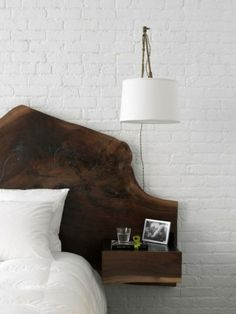 Walnut slab wall-mounted headboard with painted exposed brick