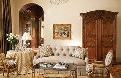 A tufted linen sofa and antique Louis XVI chairs provide comfortable seating in this living room, while antique Country French armoire creates a splendid point of focus.