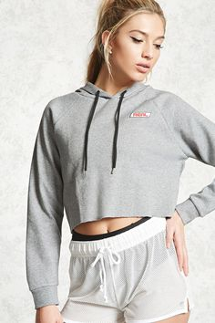 """A knit athletic hoodie featuring a raw-cut hem, raised """"Real"""" graphic on the chest, long raglan-stitched sleeves, contrast drawstrings, and a boxy silhouette."""