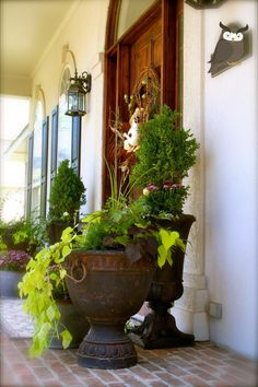 DIY patina finish for on-sale urns. Nice!  Spray with flat black paint.  Brush on with Yard and Garden durable outdoor paint and wipe off with rag.