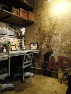 Heavily distressed walls in this masculine office space with with steampunk elements and warm, rusty tones.