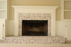 How To Update A Brick Fireplace - using watered down paint & a chip brush, this fireplace was completely transformed.   Quick & inexpensive project that makes a huge difference!