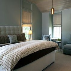Calming blue bedroom design with blue walls paint color, blue linen tufted headboard bed, gray roman shades, white & blue striped duvet, brown & blue striped pillows and blue velvet slipper chairs. Blue Grey Walls, Blue Painted Walls, Paint Walls, Blue Brown Bedrooms, Farrow And Ball Bedroom, Victorian Bedroom, Transitional Bedroom, Guest Bedrooms, Master Bedroom