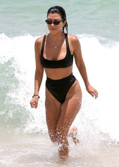 Kourtney Kardashian in a high-cut black bikini - click through for more celebrity swimsuit photos