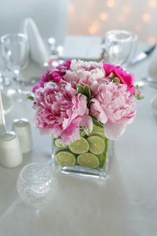 limes in vase with pink flowers. this would be so cute for a baby shower!