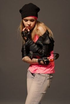 Fashion portrait of young gloved girl wearing on hat, leather jacket, blue jeans and pink t-shirt Stock Photo