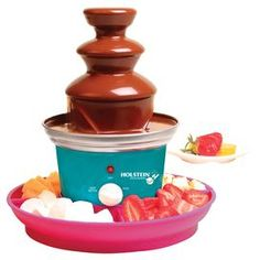 Fondue fountain with forks and a pink fondue tray.   Product: 1 Fountain and 6 fondue forksConstruction Material: Plastic and stainless steelColor: Teal and magentaFeatures:   Auger-style fountain Removable tray to hold your snacks  Dimensions: 11.4 H x 10.2 DiameterCleaning and Care: Carefully remove the tower and auger after cooling. Wash auger in warm, soapy water. Rinse and dry thoroughly. Use a damp cloth to wipe clean the rest of the appliance. Dry immediately.