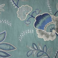 Somerford Fabric An embroidered floral fabric with thistles and foliage in teal and indigo on a turquoise background.