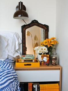 love everything aout this.                                  the brown/blue/saffron/white color combination, the old mirror with the modern sconce, real flowers, play with texture... happy happy nightstand in this bedroom.