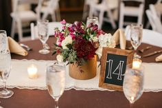 Centerpieces consisted of gold vases with jewel-toned flowers, like ruby red dahlias and scabiosa pods, with white roses and white hydrangeas. Chalkboard table numbers were displayed in gold frames.