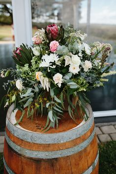 Rustic wedding ceremony flowers on a wine barrel | Jessica Turich Photography