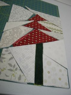 """Tree's Up, Light's On - by Sandy Gervais. I've always wanted to make this pattern. Stack, Slash, Sew Block. The shapes are cut with templates freezer paper or template plastic, then you swap the solids to make a more complex arrangement. The pattern uses 30 fat quarters (10 red, green and cream) for 51x70""""."""