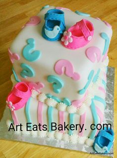 #Gender #reveal #baby #shower #cake design with blue,white and pink fondant edible baby booties, question marks and stripes.