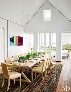 Photographs by Penelope Umbrico overlook the dining room's Jean-Michel Frank table and chairs, which were produced by Hermès   http://archdigest.com