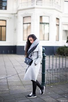 Winter Outfit Inspiration: Cozy gray coat worn with oversized plaid scarf and black Nike sneakers.