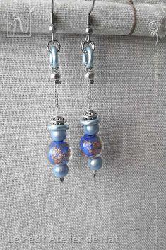 Réalisation [ Fait-Main ] avec du fil aluminium (Ø2mm), des perles magiques, une perle de verre à paillettes, des perles tibétaines, ainsi qu'une perle d'acier inox et un anneau d'aluminium. Les crochets d'oreilles sont en acier inoxydable ainsi que la chaîne. Petites boucles d'oreilles ou boucles d'oreille à assortir avec tenue et maquillage, selon l'envie. Facile à mettre et enlever, la boucle d'oreille est légère et se dandine au gré des mouvements, avec de petits tintements agréables…