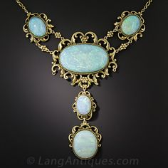 Five sizable multi-colored pastel opals (plus one more at the clasp), together weighing approximately 34 carats, are presented in regal fashion in this opulent and enchanting necklace dating from the-turn-of-the-last-century. The captivating gemstones are each framed in fanciful rococo style in warmly burnished 14K yellow gold. The necklace chain with the pair of side opals measures 15 inches and the centerpiece drops down 3 1/4 inches. A singular and stunning antique adornment.