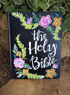 Hand painted ESV Single Column Journaling Bible. This bible is painted in the design I am calling The Kylee the front features pink and orange flowers and says, The Holy Bible. The back has Proverbs 31:25, She is clothed with strength and dignity; she laughs without fear of the future. I paint each bible by hand, so each one will look unique and be one of a kind. This design is available to be customized with your choice of verse or saying on the back cover. The Kylee This design is named…