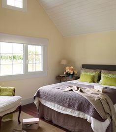 Dormitorio con techo  a dos aguas y ventanas a dos alturas. En el dormitorio