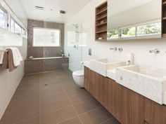 i like the tiles and the situation of the bath. Slide the shower back over the bath though, and no his and hers sinks!