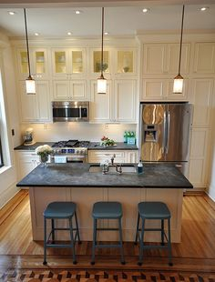 White cabinets, soapstone counters, stainless appliances, inlaid floor, bridge faucet in polished chrome, blue stools, upper display  cabinets, pendant lighting over island,large, deep sink. Classic and beautiful. Via http://www.brooklynlimestone.com/