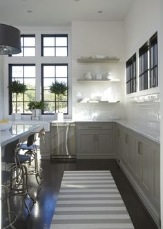 gray lower cabinets, open white shelving on top, white subway backsplash up to the ceiling, and black window panes.