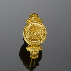 A 16th century gold signet ring The engraved crest blazoned on a wreath with a dragon's head and the intial letters EF in reverse.